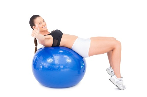 Sporty woman working out with exercise ball giving thumb up
